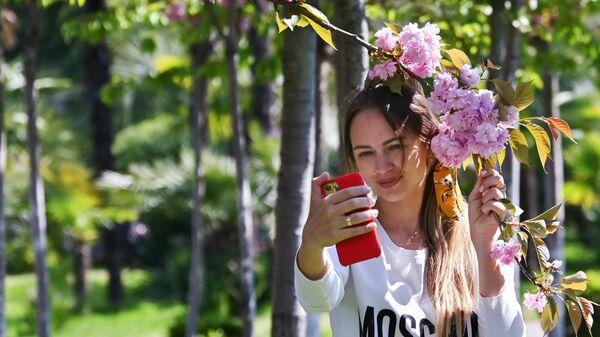 Девушка фотографируется на мобильный телефон на аллее Черешневый сад в Сочи