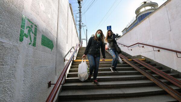 Девушки спускаются по лестнице подземного перехода в Симферополе