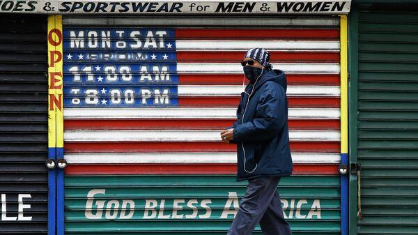 Мужчина в защитной маске у закрытого магазина в Филадельфии