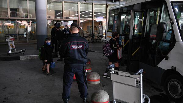Сотрудники полиции контролируют посадку пассажиров, прибывших рейсом SU 103 компании Аэрофлот из Нью-Йорка в аэропорту Шереметьево