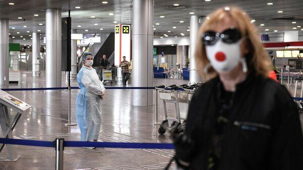 Сотрудница в защитном костюме в терминале F Международного аэропорта Шереметьево
