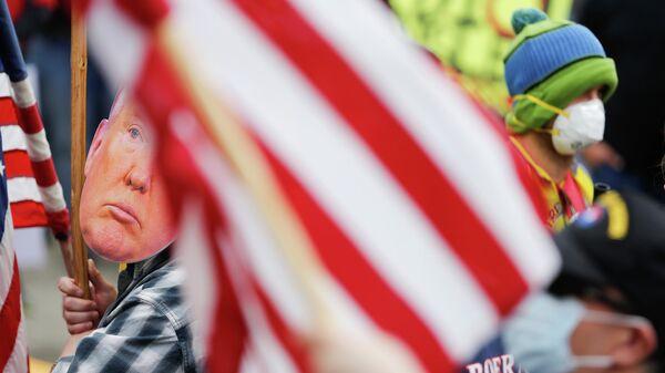 Мужчина в маске Дональда Трампа во время протеста против режима самоизоляции в Вашингтоне, США