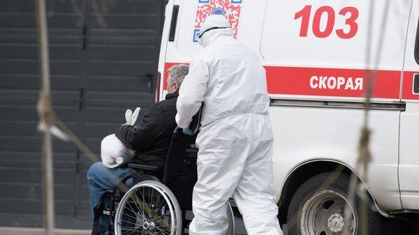 Медик везет в инвалидном кресле пациента, доставленного бригадой скорой помощи в карантинный центр в Коммунарке