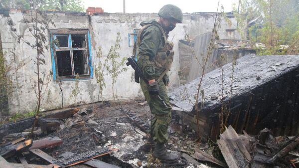 Военнослужащий НМ ДНР осматривает сгоревший дом в поселке Шахты 6-7 в Горловке