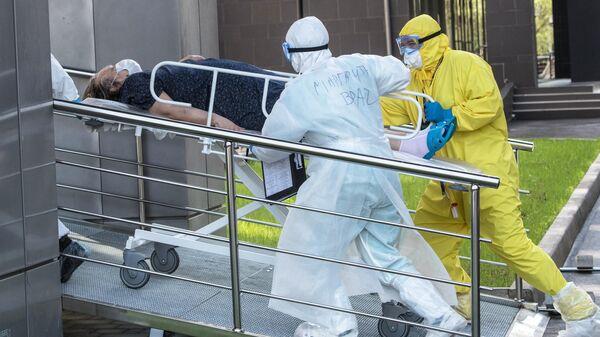 Медики транспортируют пациента с подозрением на коронавирусную инфекцию в приемное отделение национального медицинского центра эндокринологии Минздрава России в Москве
