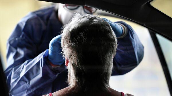 Медицинский работник берет тест на коронавирус в Нидерландах