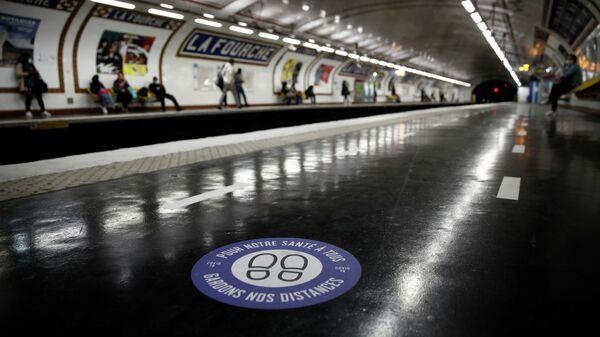 Стикер с призывом соблюдать дистанцию на одной из станций метро в Париже