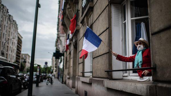 Женщина держит флаг Франции во время акции в поддержку врачей в пригороде Парижа