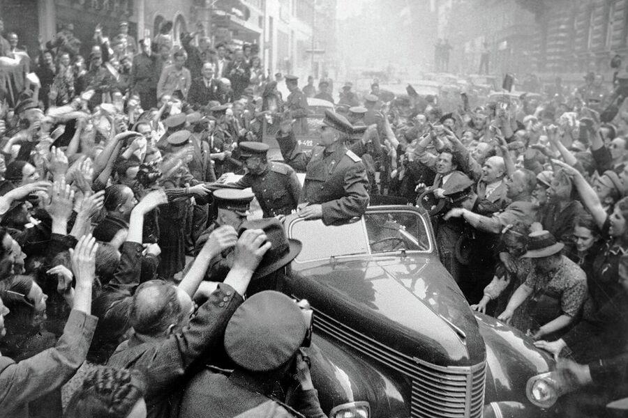 Жители Праги радостно встречают советских воинов освободителей, во главе которых маршал Иван Конев