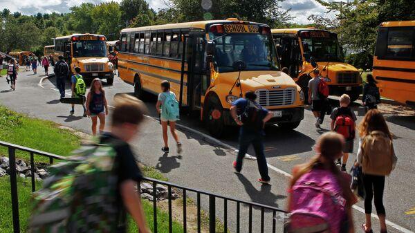 Ученики средней школы направляются к автобусам в Йорке, штат Мэн