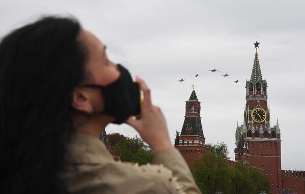 Девушка наблюдает за воздушным парадом Победы в Москве