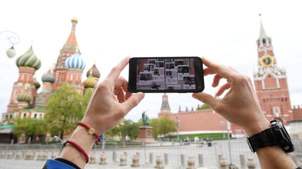 Молодой человек смотрит трансляцию акции Бессмертный полк на Красной площади в Москве