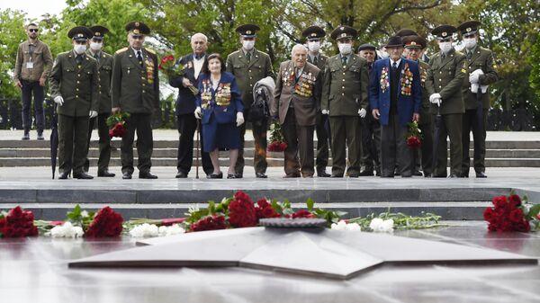 Ветераны Великой Отечественной войны возлагают цветы у Вечного огня в парке Победы во время празднования Дня Победы в Ереване