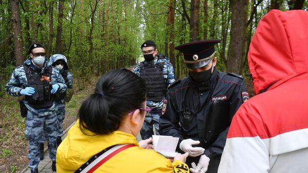 Сотрудник полиции совместно с сотрудниками Росгвардии проверяют документы у прохожих в Бирюлевском лесопарке Москвы