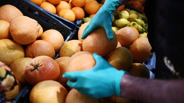 Покупатель выбирает фрукты в продуктовом магазине в Москве