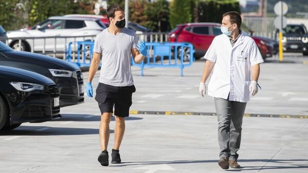 Баскетболист Барселоны идет на медицинский осмотр вместе с сотрудником медицинского отдела клуба