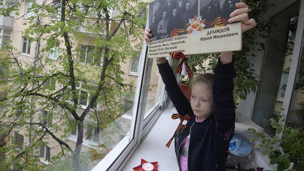 Девочка держит фотографии с портретами своих родственников - ветеранов Великой Отечественной войны