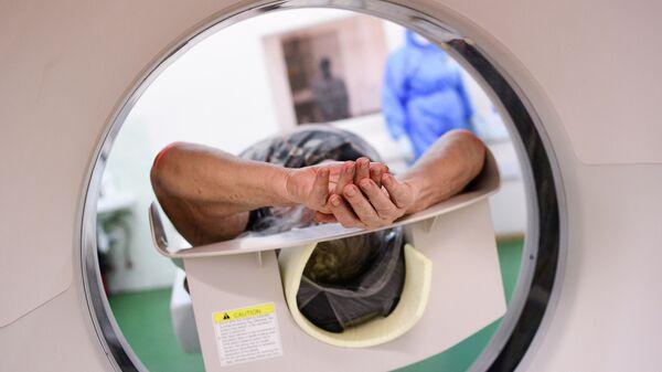 Врач готовит пациентку к процедуре компьютерной томографии легких в городской клинической больнице имени В. В. Виноградова, переоснащенной для лечения пациентов с  COVID-19