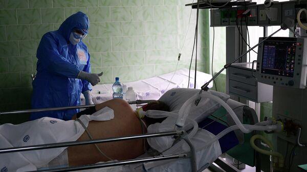 Врач и пациент в отделении реанимации и интенсивной терапии городской клинической больницы имени В. В. Виноградова, переоснащенной для лечения пациентов с COVID-19