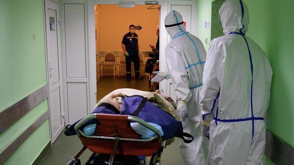 Пациент и медицинские работники в городской клинической больнице имени В. В. Виноградова, переоснащенной для лечения пациентов с COVID-19