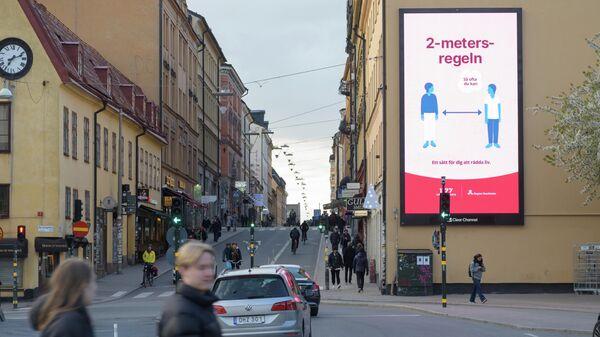 Плакат с напоминанием о социальной дистанции на фасаде дома в Стокгольме, Швеция