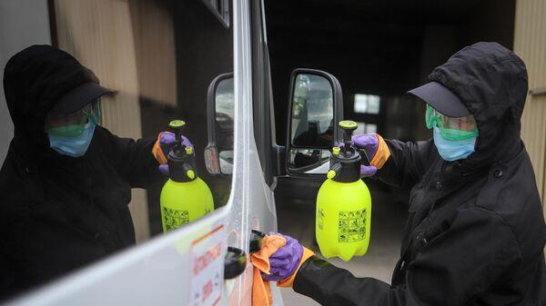 Сотрудник автовокзала проводит дезинфекцию автобуса