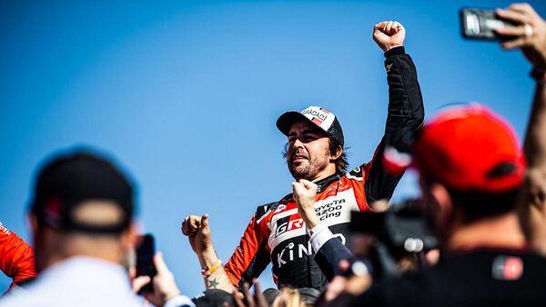 Испанский автогонщик Фернандо Алонсо празднует победу после одного из этапов ралли Дакар