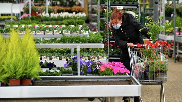Женщина в защитной маске в садовом центре в Севеноксе, Великобритания
