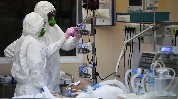 Врачи и пациент с COVID-19 в палате центральной клинической больницы РЖД-Медицина в Москве