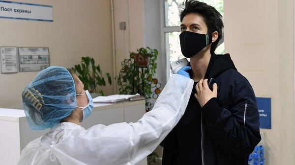 Медицинский работник измеряет температуру у мужчины перед сдачей анализа на антитела к коронавирусу COVID-19 в одной городских поликлиник в Москве