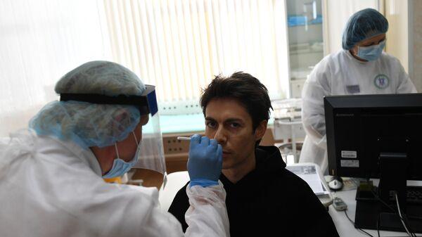 Мужчина во время взятия мазка для анализа на коронавирус COVID-19 в одной городских поликлиник в Москве