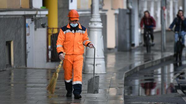 Сотрудник коммунальной службы убирает улицу в Москве