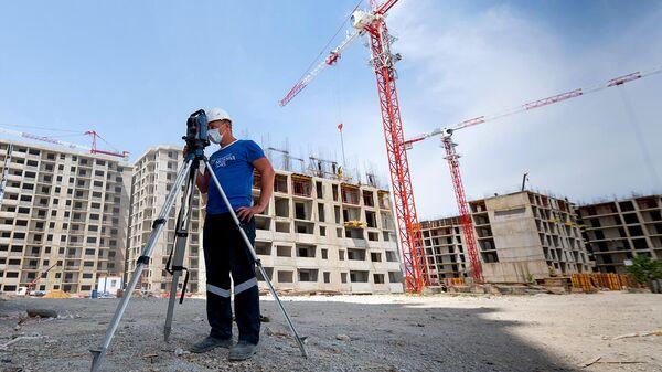 Геодезист на строительной площадке жилого комплекса