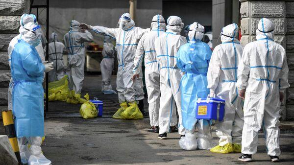 Медицинские работники проходя дезинфекцию в провинции Цзилинь, Китай