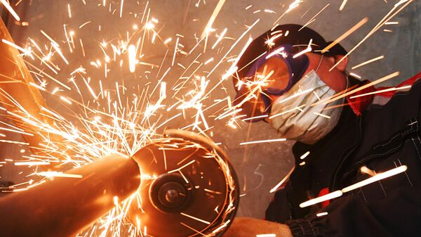 Рабочий выполняет резку металлоконструкции во время строительства жилого дома