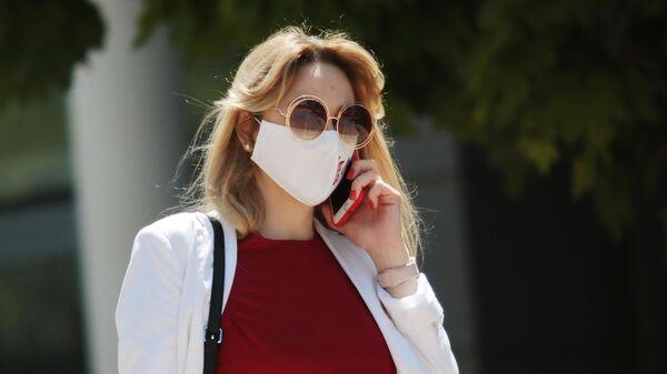 Девушка разговаривает по телефону, гуляя в защитной маске по Гагаринскому парку в Симферополе