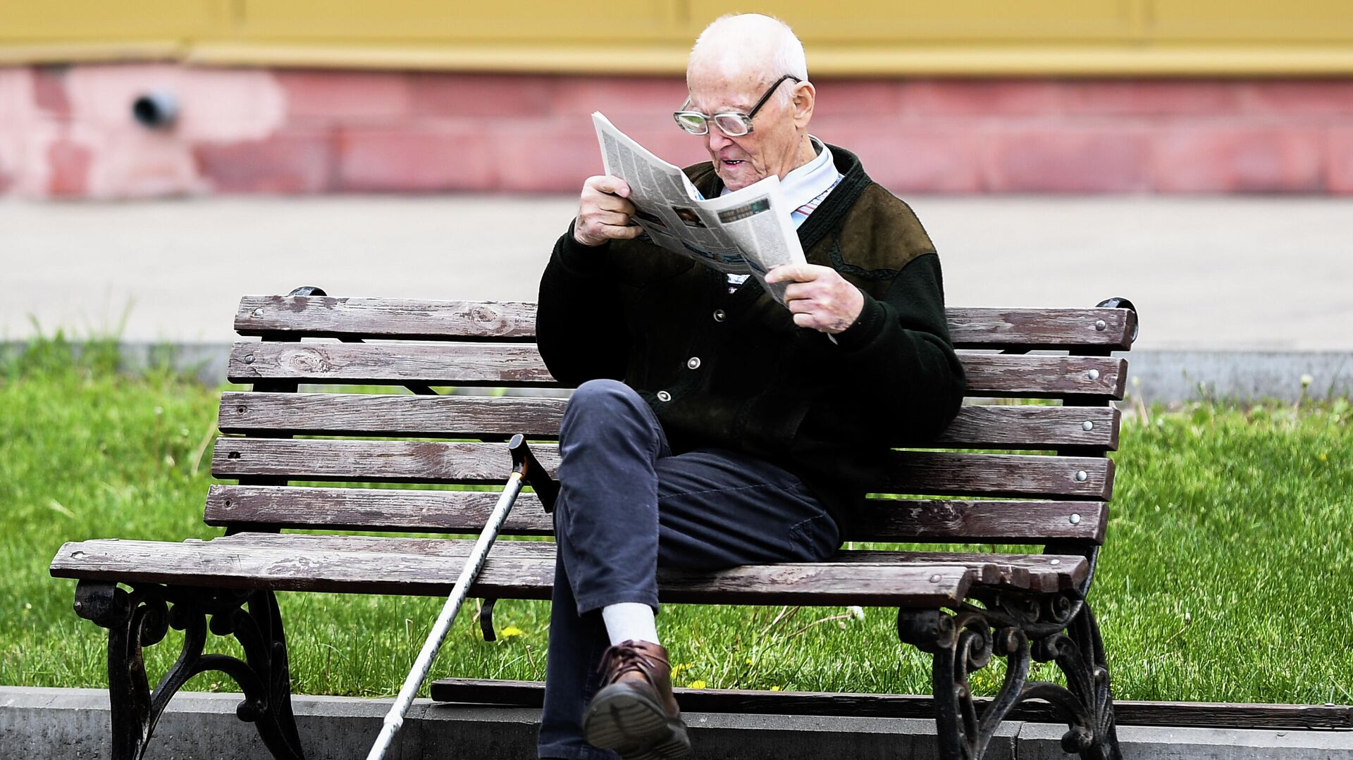 Мужчина читает газету на улице на лавочке в Москве - РИА Новости, 1920, 21.09.2020