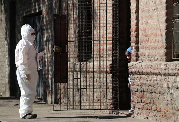 Женщина в защитном костюме разговаривает с ребенком в мигрантском районе во время введения карантинного режима в Сантьяго