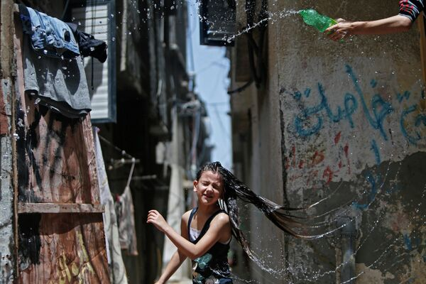 Палестинские дети играют с водой во время жары в лагере беженцев Бурейдж в Секторе Газа