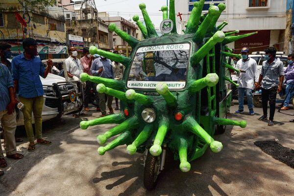 Муниципальный работник передвигается на авторикше, стилизованном под изображение коронавируса в Ченнаи, Индия
