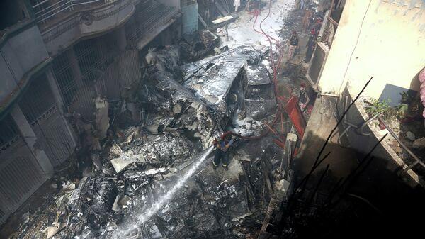 Место крушения пассажирского самолета в жилом районе недалеко от аэропорта в Карачи