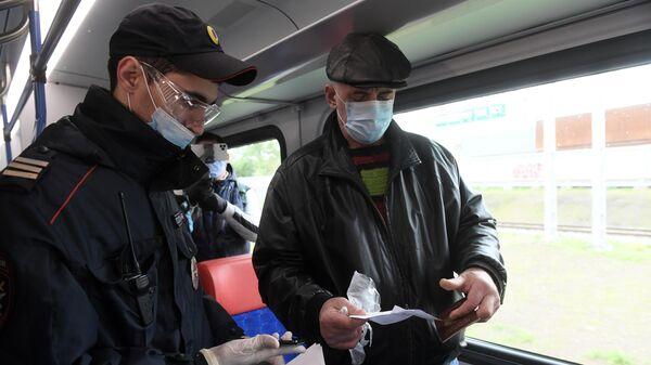 Сотрудник полиции проверяет документы у пассажира в поезде Московских центральных диаметров