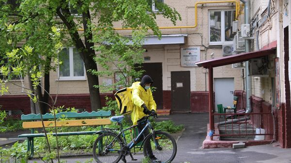 Курьер службы доставки Яндекс Еда у подъезда жилого дома на Ленинском проспекте в Москве