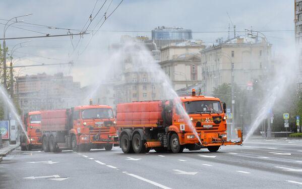 Автомобили коммунальных служб во время дезинфекции проезжей части дорог в Москве