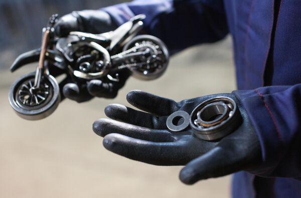 Мастер Станислав Черновасиленко выбирает подходящие по размеру подшипник и шайбу для будущего колеса миниатюрной копии мотоцикла