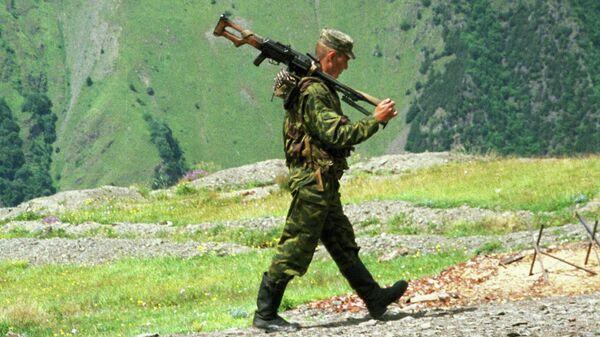 Пограничник Итум-Калинского отряда, охраняющего чеченский участок российско-грузинской границы, идет с пулеметом на боевое дежурство