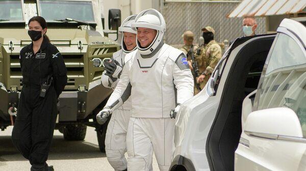 Астронавты Дуглас Херли и Роберт Бенкен (справа) - члены экипажа корабля Crew Dragon перед тем, как отправиться на стартовую площадку для полета на МКС