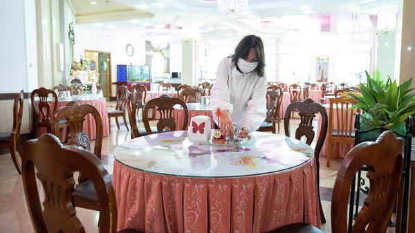 Сотрудница санатория Октябрьский в Сочи укомплектовывает столы в ресторане
