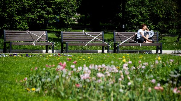 Девушка отдыхает на скамейке в сквере у Новодевичьего женского монастыря в Москве
