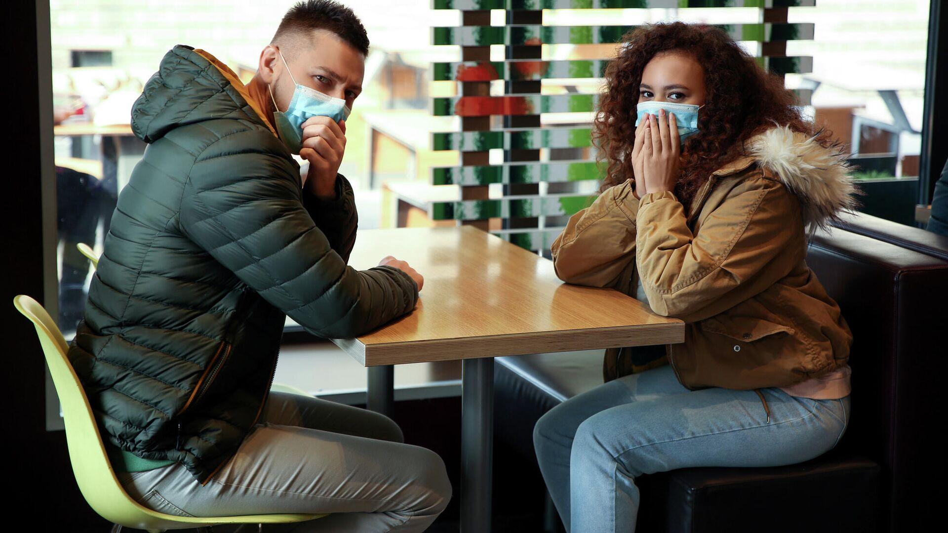 Молодые люди в защитных медицинских масках за столиком в кафе - РИА Новости, 1920, 27.01.2021